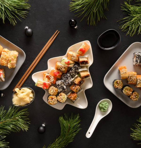 Festive Christmas dinner with sushi set with Xmas decoration on black.
